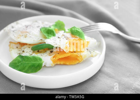 Plate with delicious over hard fried eggs on tablecloth - Stock Photo