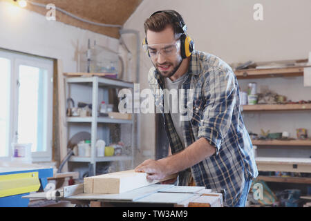 Young carpenter working with circular saw in shop - Stock Photo