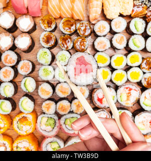 top view of chopsticks with tuna nori roll over set of sushi and rolls on wooden table - Stock Photo