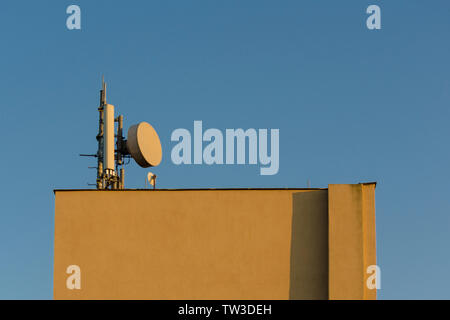 A television telecommunications antenna on clear blue day sky mounted on the roof of yellow square building as a background. Minimalistic design with - Stock Photo
