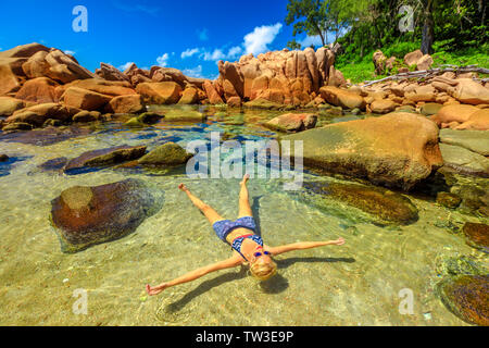 La Digue, Anse Caiman, natural pool. Blonde young woman in bikini sunbathing on crystal water of swimming pools at remote Anse Caiman protected by - Stock Photo