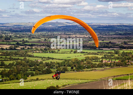 Paraglider with yellow parachute gliding over green landscape - Stock Photo