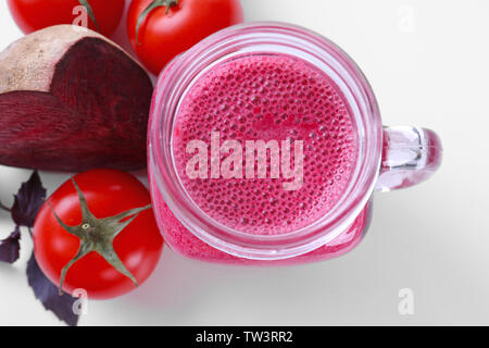 Mason jar with fresh vegetable juice an d ingredients on white background - Stock Photo