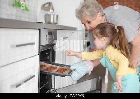 Cute little girl and her grandmother taking out cookies from oven on kitchen - Stock Photo