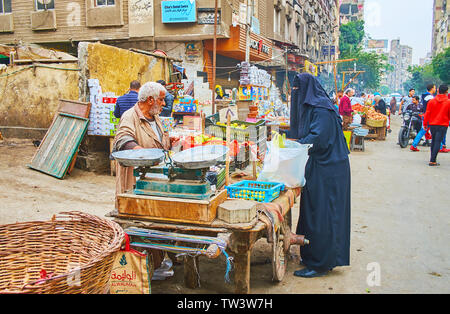 CAIRO, EGYPT - DECEMBER 22, 2017: The muslim woman, wared in black niqab and abaya, chooses fresh lemons and oranges in small stall of Souq As Sebaeyi - Stock Photo