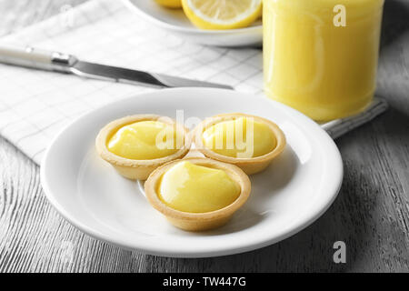 Plate with tasty lemon cookies on wooden table - Stock Photo