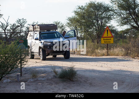 white 4x4 off road overland camping vehicle with a man getting in at the main entrance gate to Nossob rest camp, Kgalagadi Transfrontier National Park - Stock Photo