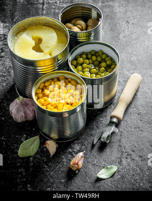Canned pineapples, green peas, corn and mushrooms in open cans. On dark rustic background - Stock Photo