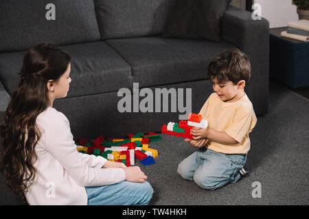 cute kid looking at toddler brother playing with colorful toy blocks in living room - Stock Photo