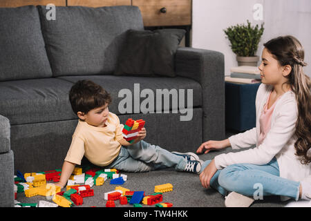 adorable child looking at toddler brother playing with colorful toy blocks in living room - Stock Photo