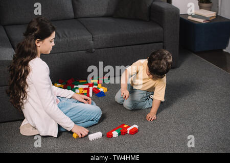cute child looking at toddler brother playing with colorful toy blocks in living room - Stock Photo