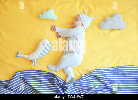 Cute little baby with toys sleeping on bed at home - Stock Photo