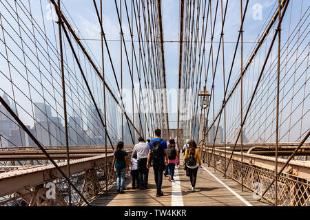 USA, New York. May 4th, 2019. Brooklyn Bridge and tourists walking, Manhattan skyline on the background. Blue sky, spring sunny day - Stock Photo