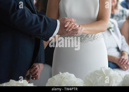 Bride and Groom exchanging rings and holding hands on their wedding day as they get married, no faces can be seen, just hands. - Stock Photo