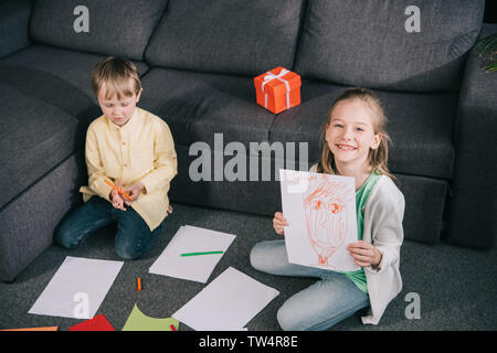 cheerful girl showing drawing and smiling at camera while sitting on floor near brother - Stock Photo