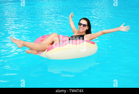 Beautiful young woman on inflatable donut in swimming pool - Stock Photo