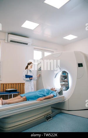 radiologist in white coat operating ct scanner while patient lying on ct scanner bed - Stock Photo