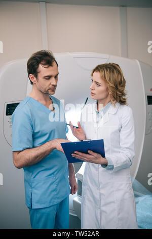 two serious radiographers talking while examining radiology diagnosis - Stock Photo