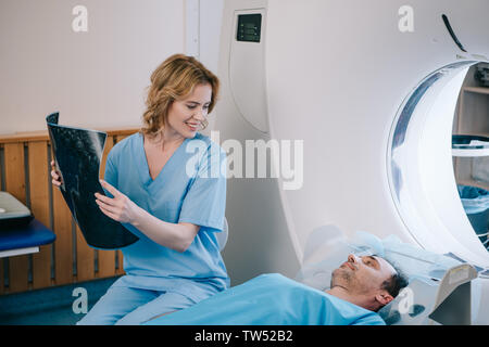 beautiful smiling doctor holding radiology diagnosis and looking at man lying on ct scanner bed - Stock Photo