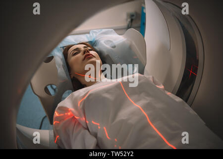beautiful woman lying on ct scanner bed during tomography test in hospital - Stock Photo