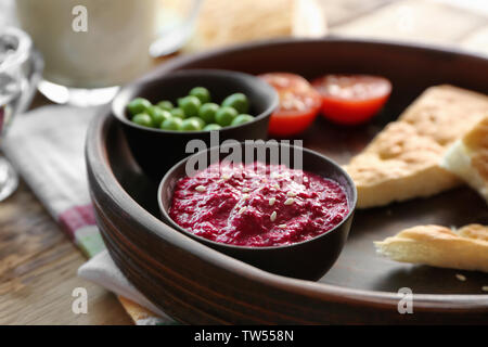 Bowl with delicious beet hummus, peas, tomato and bread on table - Stock Photo
