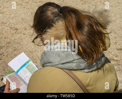 BUDAPEST, HUNGARY - MARCH 2018: Person reading a tourist guide book on a sunny day in Budapest. - Stock Photo
