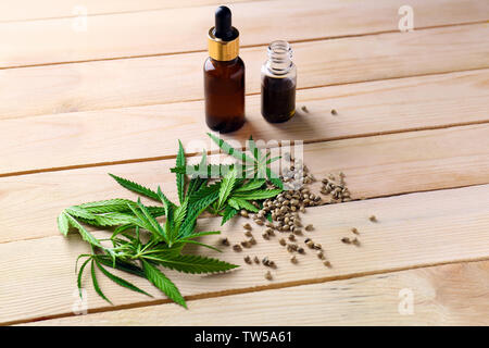 Hemp leaves and bottles of oil on wooden background - Stock Photo
