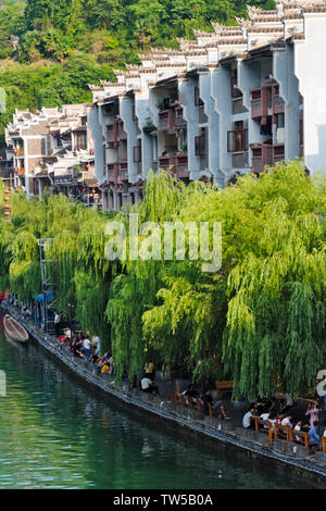 Traditional houses along Wuyang River and Dragon Boat Race on the river during Duanwu Festival, Zhenyuan, Guizhou Province, China - Stock Photo