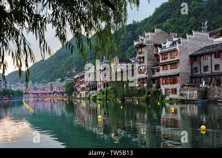Traditional houses along the Wuyang River with reflection in the water, Zhenyuan, Guizhou Province, China - Stock Photo