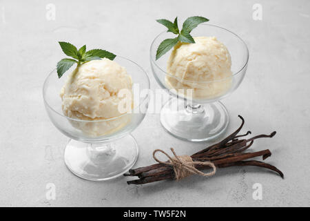 Delicious vanilla ice cream in glass dessert bowls on light background - Stock Photo