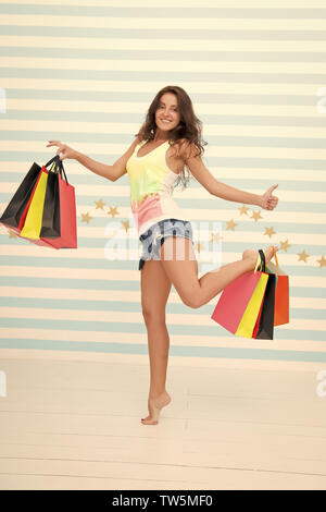 she made a right choice. shopping girl with happy face and thumb up. great sale. time for shopping. happy girl with paperbags on colorful background. carefree and excited buyer showing thumb up - Stock Photo