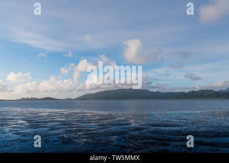 Blue sky and white clouds reflected in a pattern of water ways through tidal flats under forested mountains and hills on the Oregon coast near Tillamo - Stock Photo