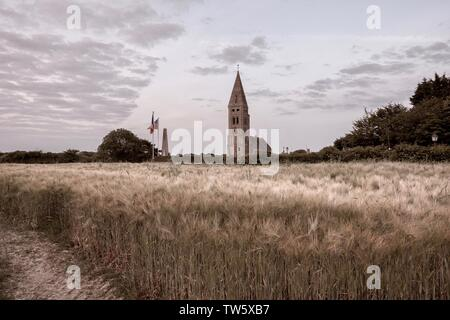 Church and memorial in famous French village Colleville sur Mer seen at the distance from a wheat field at sunset - French countryside - Stock Photo
