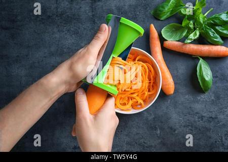 Woman using vegetable spiral slicer to make carrot spaghetti - Stock Photo