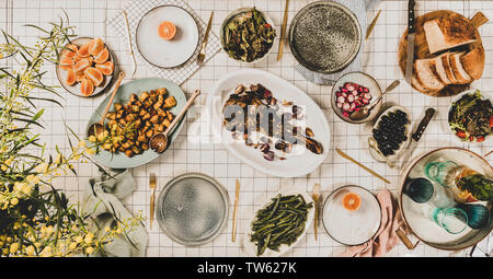 Family, friends gathering dinner. Flat-lay of roasted lamb shoulder, salads, baked vegetables, snacks, bread, lemonade in jug and blooming mimosa bran - Stock Photo