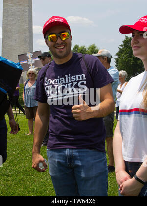 Washington, D.C., USA. 1st June, 2019. With the Washington Monument in the background at the National March To Impeach on 1 June, 2019, a young, grinning man faces the camera, wearing sunglasses and a red 'Make America Great Again' baseball cap/hat, and gives a thumbs-up sign in front of the words 'Socialism Sucks' on his t-shirt. The young woman next to him, partially visible, wears the same cap and smiles slightly while facing left. They were two of several pro-Trump counterprotesters at the People Demand Action-organized demonstration on the Washington Monument Grounds. Kay Howell/Alamy - Stock Photo