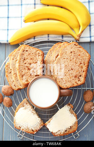 Sliced banana bread with nuts on wooden table - Stock Photo