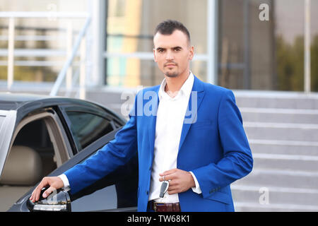 Young businessman with key near car - Stock Photo