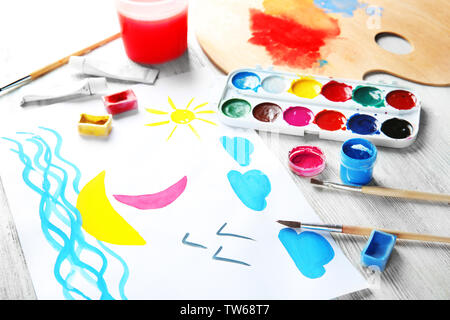 Child's painting of sailing ship on table - Stock Photo