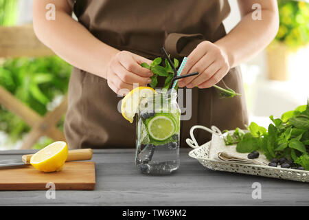 Woman preparing infused water with fruits in mason jar - Stock Photo