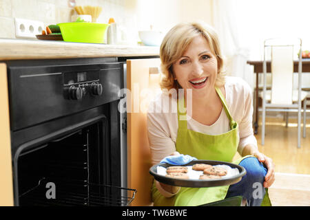 Woman with cookies near oven in kitchen - Stock Photo
