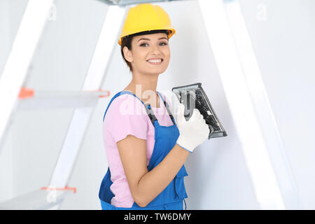 Young female decorator working with plastering trowel indoors - Stock Photo