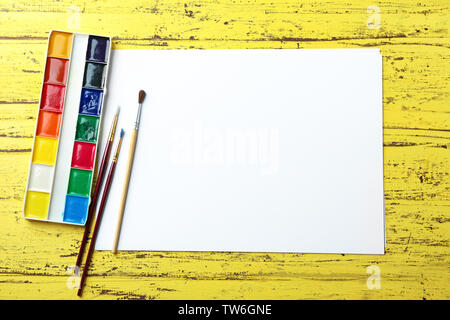 Blank sheet of paper and watercolors on yellow background - Stock Photo
