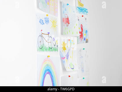 Different children's drawings on white wall - Stock Photo