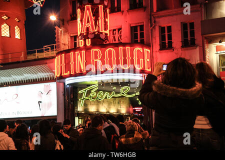 PARIS, FRANCE - JANUARY 1, 2008: Tourists taking pictures in front of Moulin Rouge at night, one of the most famous Pigalle cabarets and show runners - Stock Photo