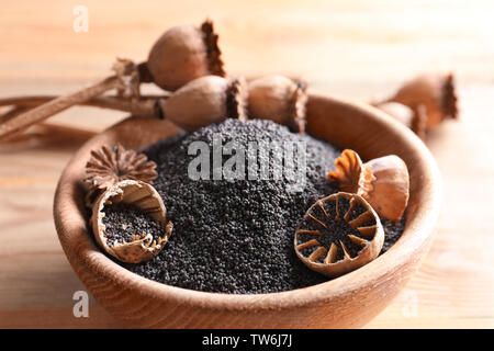 Poppy heads and seeds in bowl on table, closeup - Stock Photo
