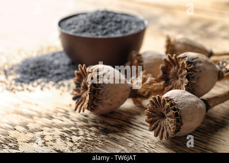Dried poppy heads and seeds in bowl on table, closeup - Stock Photo