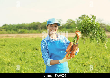 Young female farmer holding ripe carrots in field - Stock Photo
