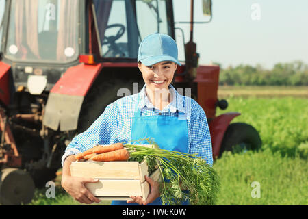 Female farmer holding wooden box with carrots in field - Stock Photo