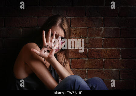Battered young woman with written words 'Help me' on palm near brick wall - Stock Photo